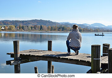 Girl on the wooden jetty against a lake. Switzerland