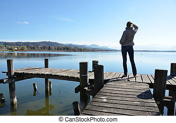 Girl on the wooden jetty at a lake