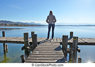 Girl on the wooden jetty at a lake. Switzerland
