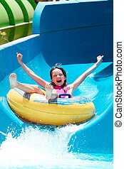 Girl on water slide  - A young girl on a water slide.