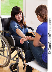 Girl on wheelchair talking with female friend, vertical
