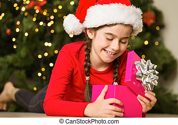 Girl opening a gift at christmas