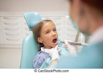 Girl opening mouth while dentist examining teeth