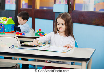 Girl Opening Popup Book at Desk