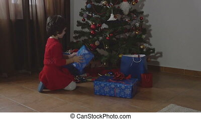 Girl opening the Christmas present - Young beautiful girl...