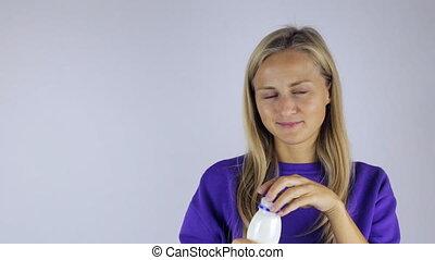 Girl opens a bottle of yogurt