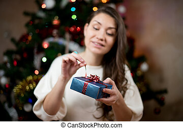 girl opens a gift for the new year. Gift Focus