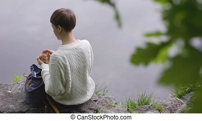 Girl opens backpack. Rear view of a woman sitting on rocks near the pond. Montage video.