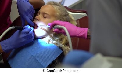 Girl opens mouth wide during drilling caries in teeth. Doctor hands working with drill and assistant nurse holding equipment. Camera movement forward shot with gimbal.