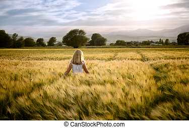 Girl or teen walking through wheat field, facing sunset.