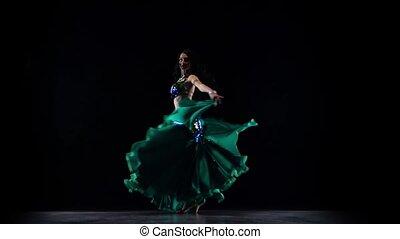 Girl oriental belly dancer. Black background. Slow motion -...