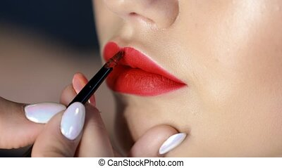 girl paint lips red lipstick in the beauty salon
