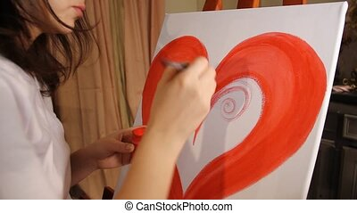 girl painting a heart - close up of woman artist painting a...