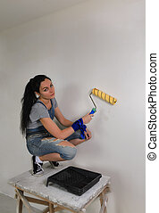 Girl painting a wall in her house