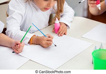 Girl Painting At Desk In Preschool