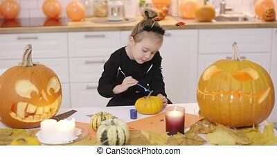 Girl painting pumpkin - Little girl in cute Halloween...