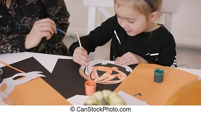 Girl painting pumpkin - Cute little girl in Halloween...