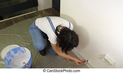 girl painting the wall with a brush