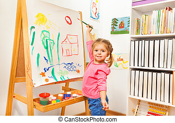 Girl painting with green brush at the easel