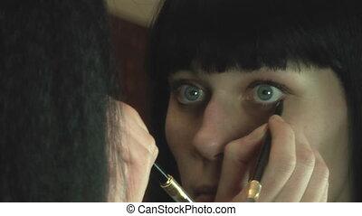 Girl paints eyelashes brush apply makeup to the face mascara on her eyes