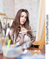 girl paints in workshop