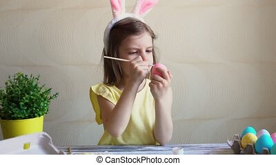 girl paints the Easter eggs