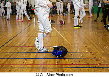 Girl participant in the fencing competition on swords is in the center of gym