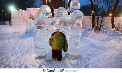 girl passes some times through gate in form of ice sculptures representing man and woman