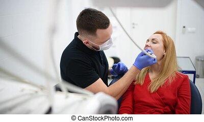 Girl patient at dentist cabinet make oral hygiene dental...