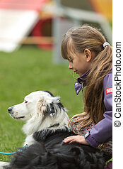 Girl patting dog - Girl patting a white and black purebred...