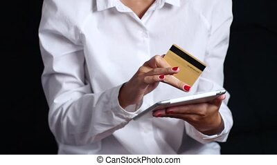 Girl pays for an online purchase with a tablet and credit card. Black. Close up