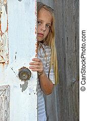 girl peeking around old door - Young girl peeking around old...