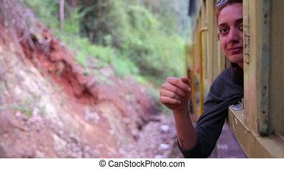 Girl peeking out of train - female tourist peeking out of...