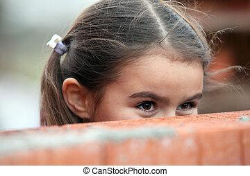 Girl peeking over a brick wall