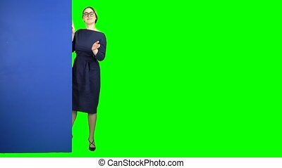 Girl peeks out and points at the billboard. Green screen -...