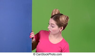 Girl peeks out from behind a blue board and shows a ok....