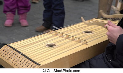 Girl performing music with traditional string instrument at...