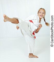 Athlete in a kimono performs a kick leg circular