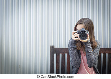 Girl Photographer Sitting and Pointing Camera
