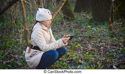 Girl photographing flowers in the spring forest
