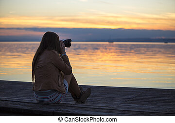 girl photographing sunset at lake in autumn