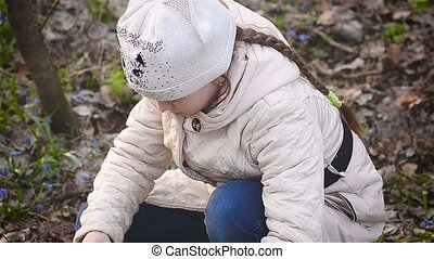 Girl photographs of snowdrops in the forest
