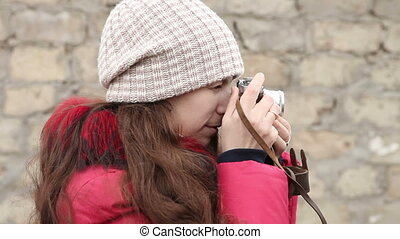 Girl photographs on a film camera, side view HD