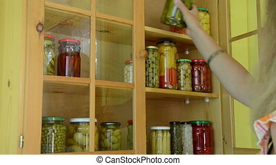 girl pickled food shelf - Girl put glass pots with freshly...