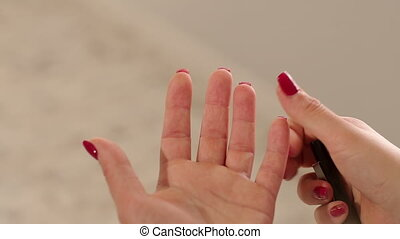 Girl piercing his finger with a scarifier to check the level...