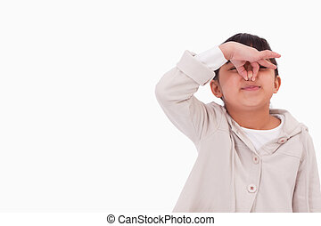 Girl pinching her nose against a white background
