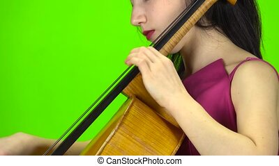 Girl pins the cello with her fingers. Green screen. Side...