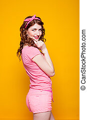 girl pinup-style in a pink dress