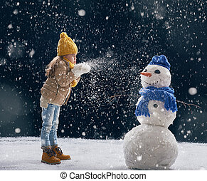 girl plaing with a snowman