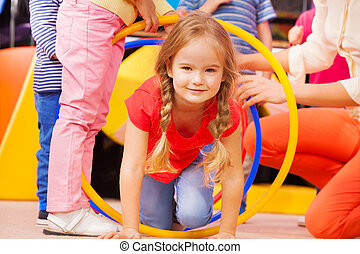 Girl play a game in kindergarten crawl though hoop